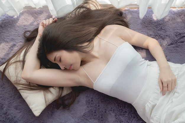 Young asian woman sleeping and showing armpits.
