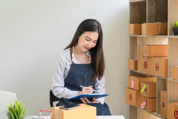 젊은 아시아 여성 중소기업 소유주와 펜을 들고 집에서 온라인 판매 주문을 받고 있습니다.