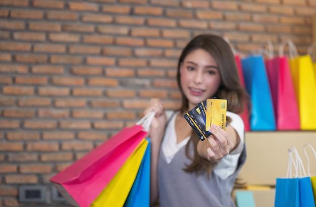Молодая азиатская женщина улыбается с успехом sme бизнес и хозяйственная сумка в руке для онлайн-покупок дома.