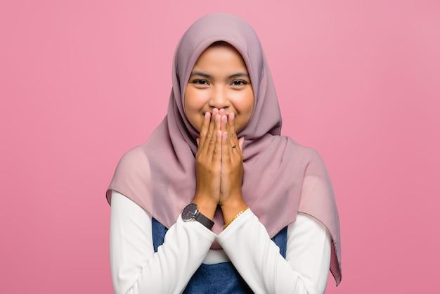 Молодая азиатская женщина улыбается и прикрывает рот рукой