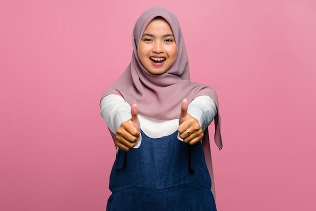 Молодая азиатская женщина улыбается и дает большие пальцы руки