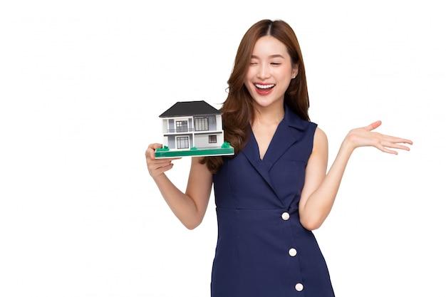 웃 고 흰색 배경, 부동산 및 가정 보험 개념 위에 고립 된 집 샘플 모델을 들고 젊은 아시아 여자