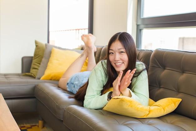젊은 아시아 여자 웃 고 친절 하 게 찾고, 앞으로 손으로 2 또는 초를 보여주는 카운트 다운