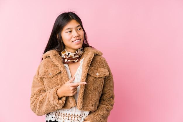 Молодая азиатская женщина усмехаясь и указывая в сторону, показывая что-то на пустом пространстве.