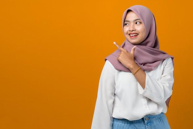 笑顔と空のスペースを指して若いアジアの女性