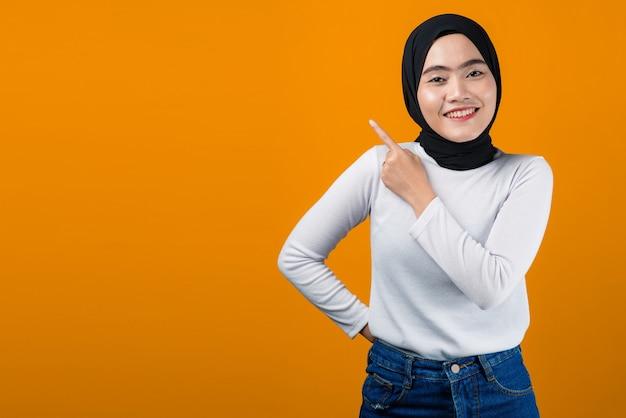 웃 고 빈 공간을 가리키는 젊은 아시아 여성