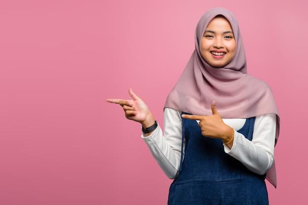 Молодая азиатская женщина улыбается и указывает в сторону