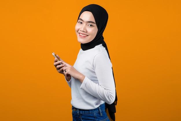 Молодая азиатская женщина улыбается и использует мобильный телефон