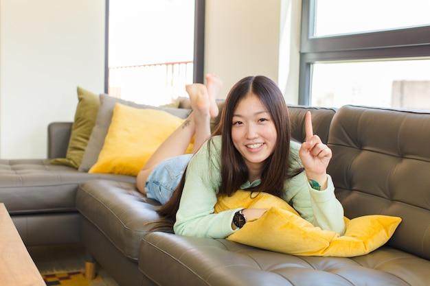 유쾌하고 행복하게 웃는 젊은 아시아 여성, 공간을 복사하려면 한 손으로 위쪽을 가리키는