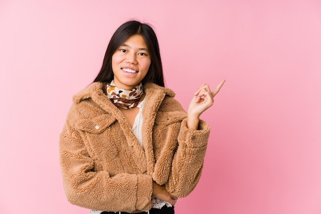 Молодая азиатская женщина усмехаясь жизнерадостно указывая с указательным пальцем прочь.