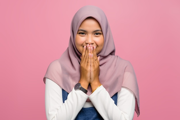 Young asian woman smiling and covering mouth with hand