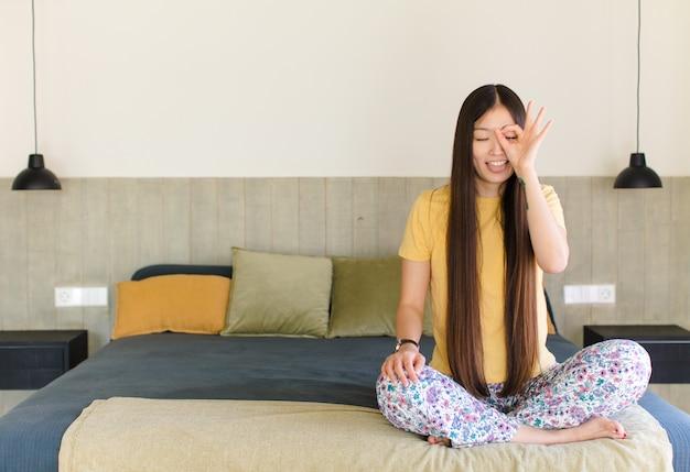 Молодая азиатская женщина улыбается, чувствует себя беззаботной, расслабленной и счастливой, танцует и слушает музыку, веселится на вечеринке