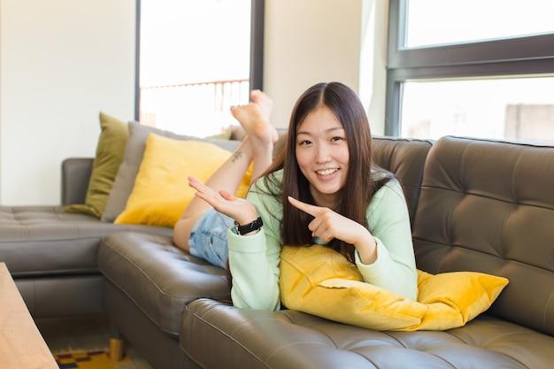 笑顔、幸せ、のんきと満足を感じ、側面のコピースペースのコンセプトやアイデアを指している若いアジアの女性