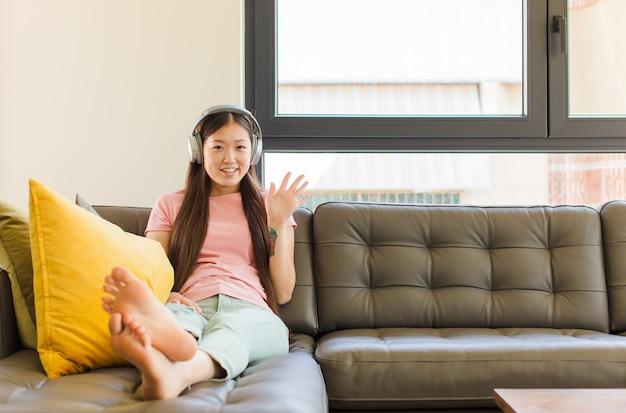행복 하 고 유쾌 하 게 웃 고, 손을 흔들며 젊은 아시아 여자
