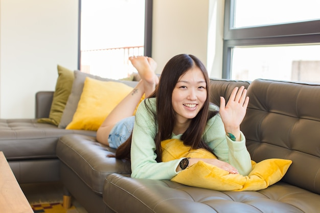 Young asian woman smiling happily and cheerfully, waving hand, welcoming and greeting you, or saying goodbye