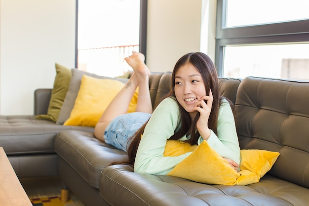 Young asian woman smiling happily and daydreaming or doubting, looking to the side