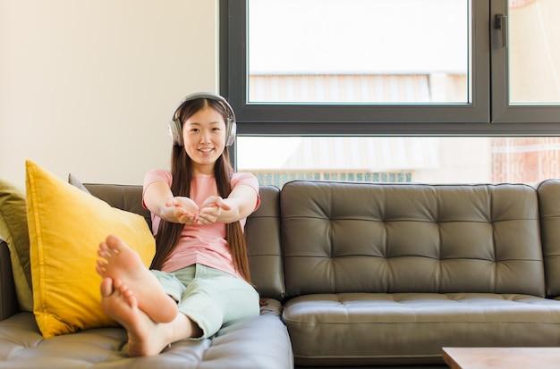 フレンドリーで自信に満ちた、前向きな表情で幸せに笑って、オブジェクトやコンセプトを提供し、示す若いアジアの女性