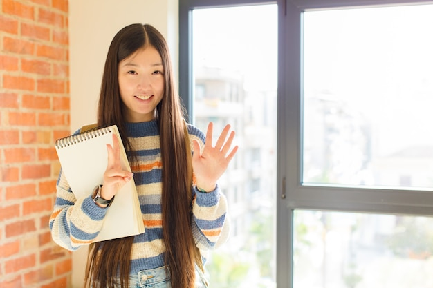 Young asian woman smiling and looking friendly, showing number seven or seventh with hand forward, counting down