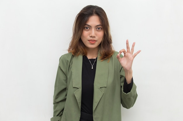 Young asian woman smiling and making ok sign with hand gesture