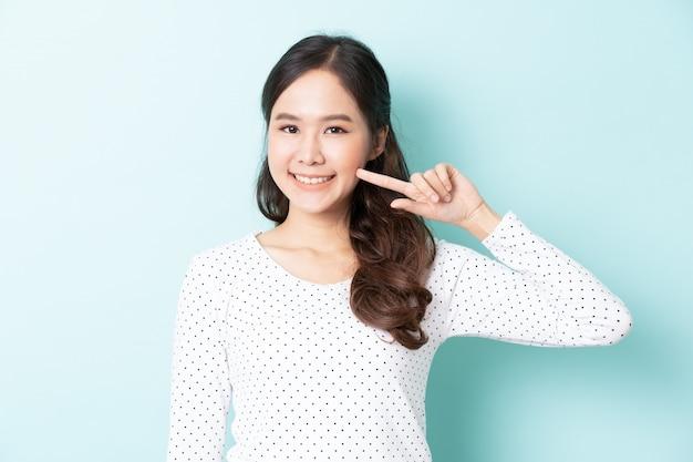 青色の背景に笑みを浮かべて若いアジア女性