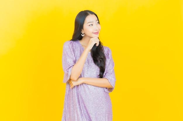 黄色に笑って若いアジアの女性