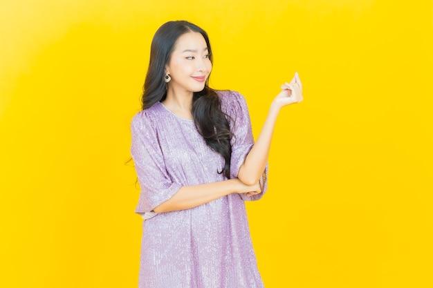 Молодая азиатская женщина улыбается на желтом