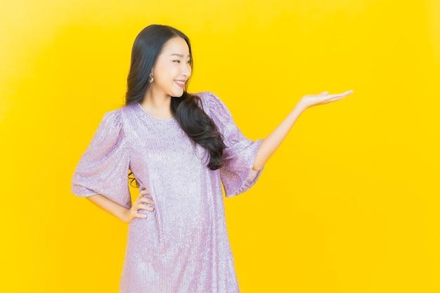Молодая азиатская женщина улыбается на желтом Бесплатные Фотографии