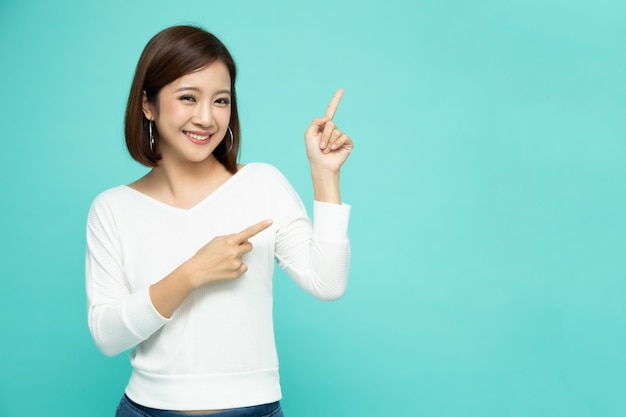 Young asian woman smiling and pointing to blank empty background.