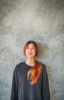 Young asian woman smiling portrait infront of a gray cement wall .