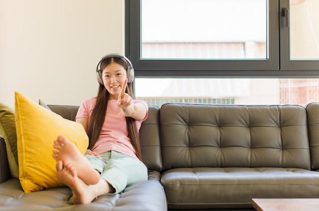 자랑스럽게 웃고 자신있게 넘버 원을 만드는 젊은 아시아 여성