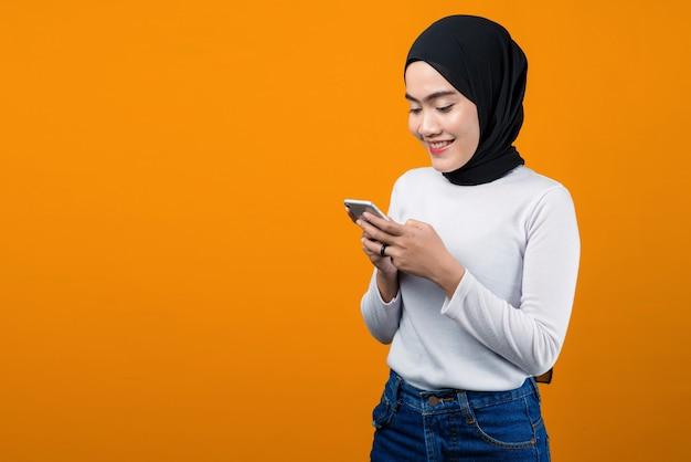 웃 고 휴대 전화를 사용 하여 젊은 아시아 여자