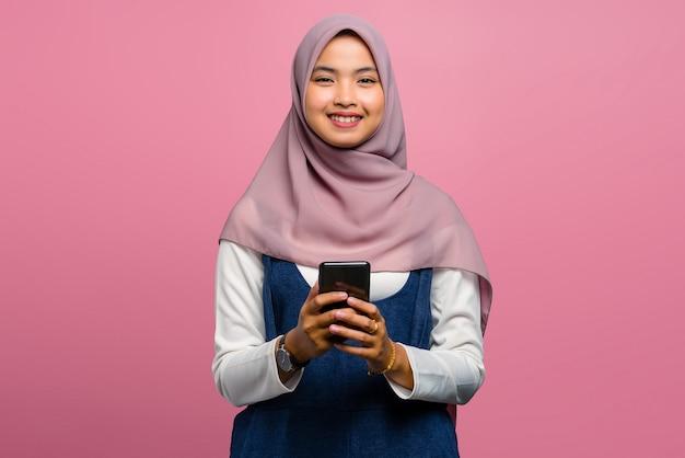 携帯電話を使用して笑っている若いアジアの女性