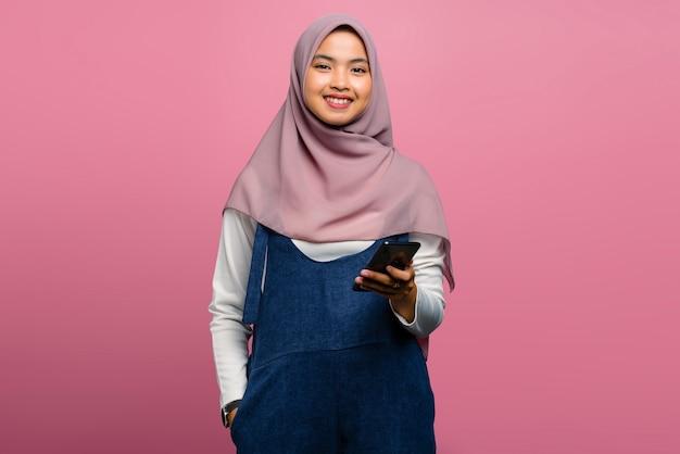 휴대 전화를 사용 하여 웃 고 젊은 아시아 여성