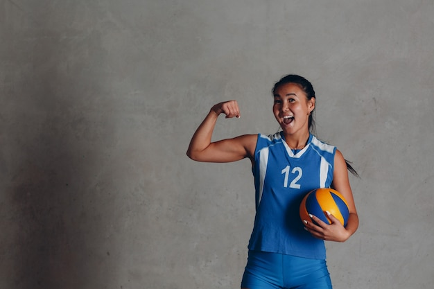 Young asian woman smiling  volleyball player in blue uniform with ball