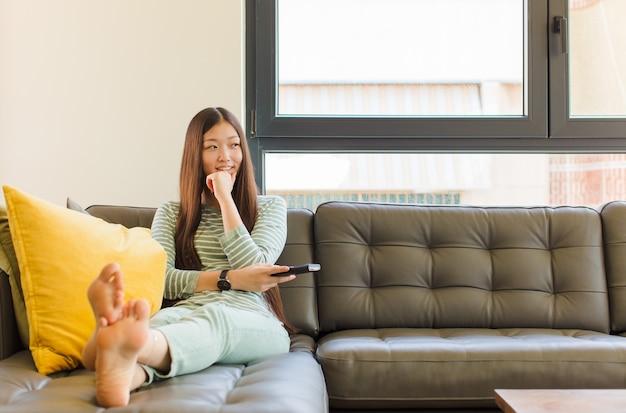 턱에 손으로 행복하고 자신감있는 표정으로 웃고, 궁금해하고 측면을 찾고 젊은 아시아 여자