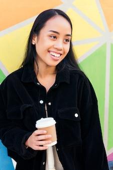 화려한 벽 앞에서 테이크 아웃 커피와 함께 웃고 있는 젊은 아시아 여성