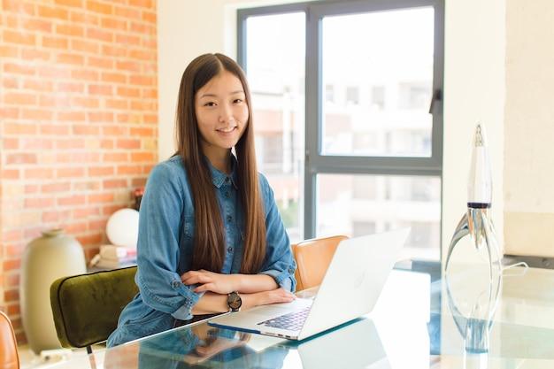 교차 팔과 행복, 자신감, 만족 표현, 측면보기와 함께 웃 고 젊은 아시아 여자