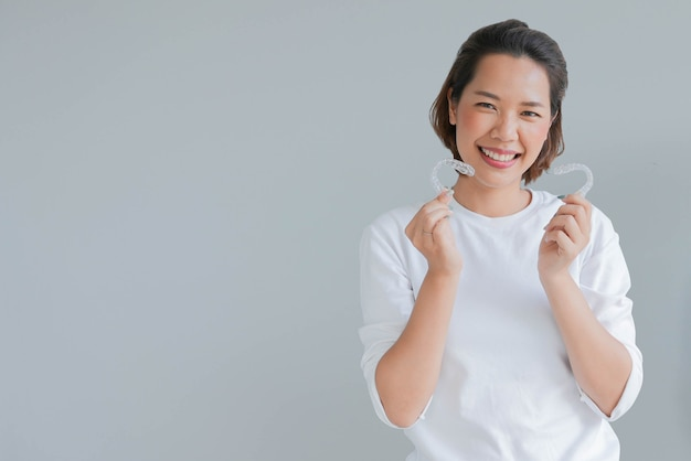 Young asian woman smiling with dental aligner retainer invisible isolated on gray background