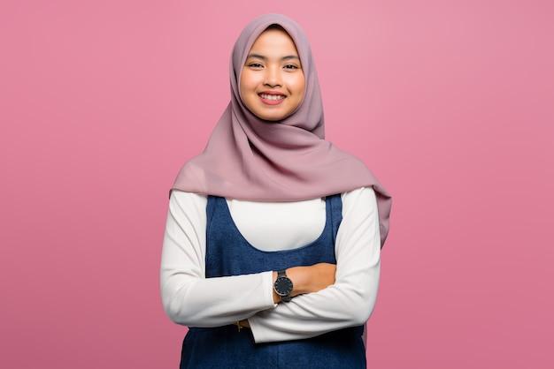 Молодая азиатская женщина улыбается сложенной рукой