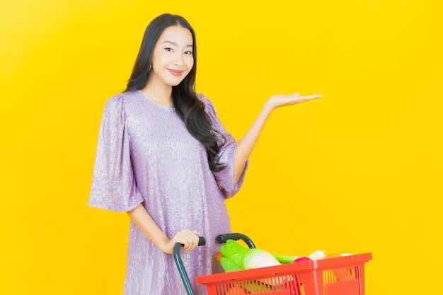 노란색 슈퍼마켓에서 식료품 바구니와 함께 웃 고 젊은 아시아 여자