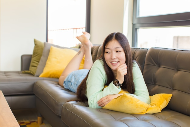 Young asian woman smiling with a happy, confident expression with hand on chin, wondering and looking to the side