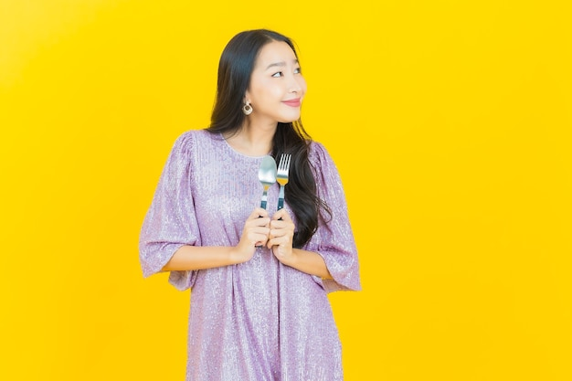 Young asian woman smiling with spoon and fork on yellow