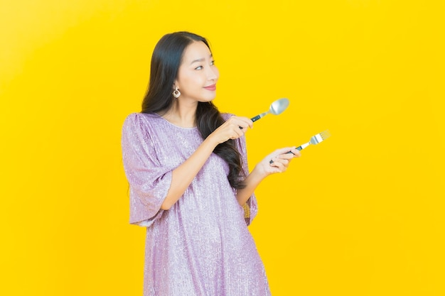 Giovane donna asiatica sorridente con cucchiaio e forchetta su yellow