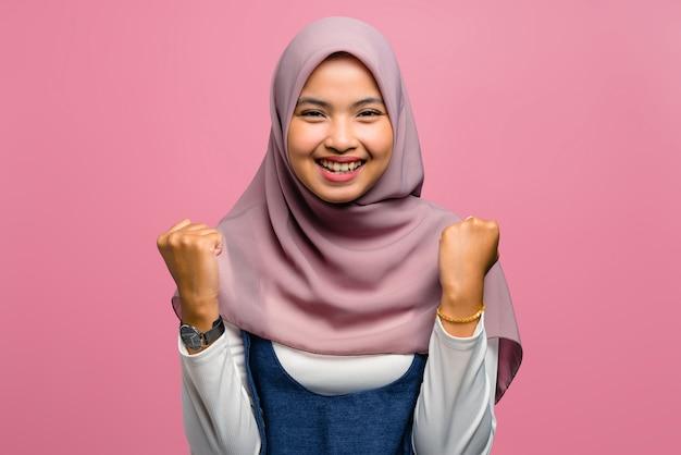 Молодая азиатская женщина улыбается с выражением успеха
