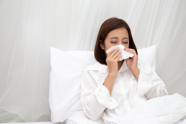 Young asian woman sneezing in a tissue on the white bed at bedroom