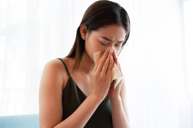 Young asian woman sneezing