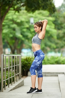 Young asian woman in sports top and leggings doing arm stretch in park