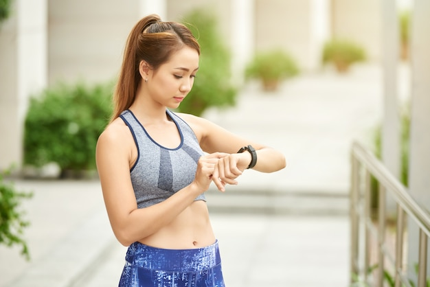 Young asian woman in sports top and leggings standing in street and setting up smart watch