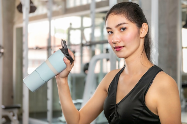 Young asian woman in sportswear drinking water after workout at fitness gym