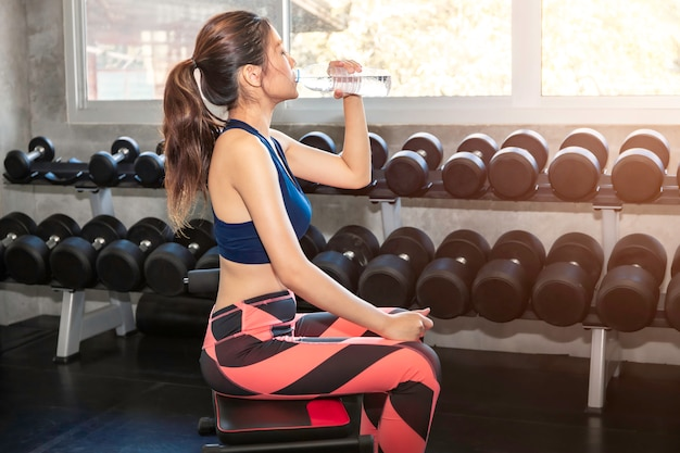 Young asian woman in sportswear drinking water after workout at fitness gym.